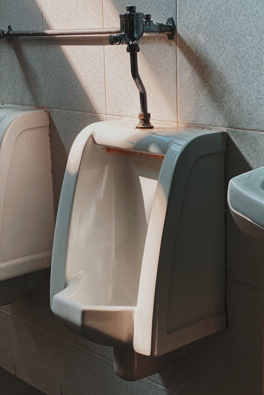 shallow focus photo of white ceramic urinal bowl